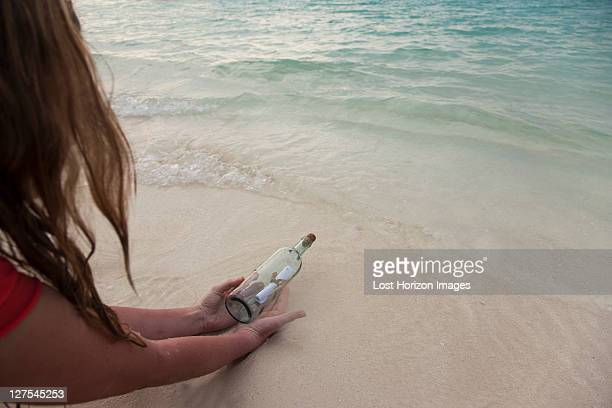 Woman with message in a bottle at beach