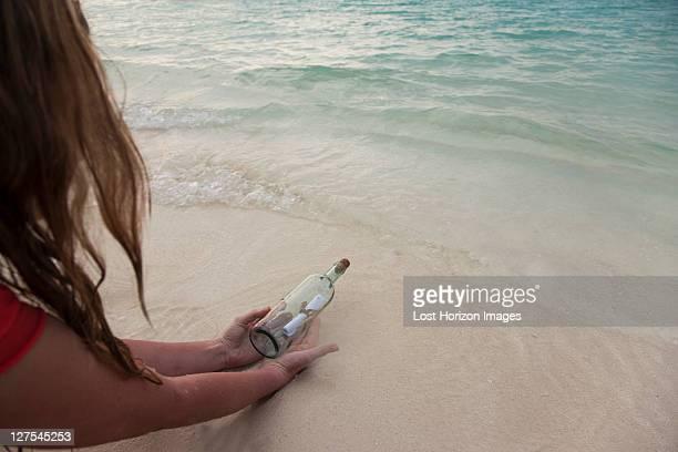 Femme avec message dans une bouteille sur la plage