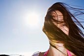 Woman with messy hair blowing on windy day