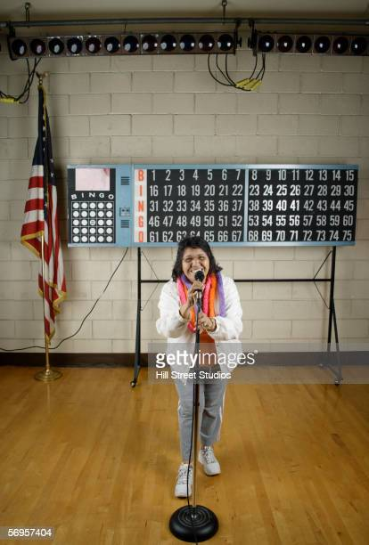 Woman with microphone in front of bingo board