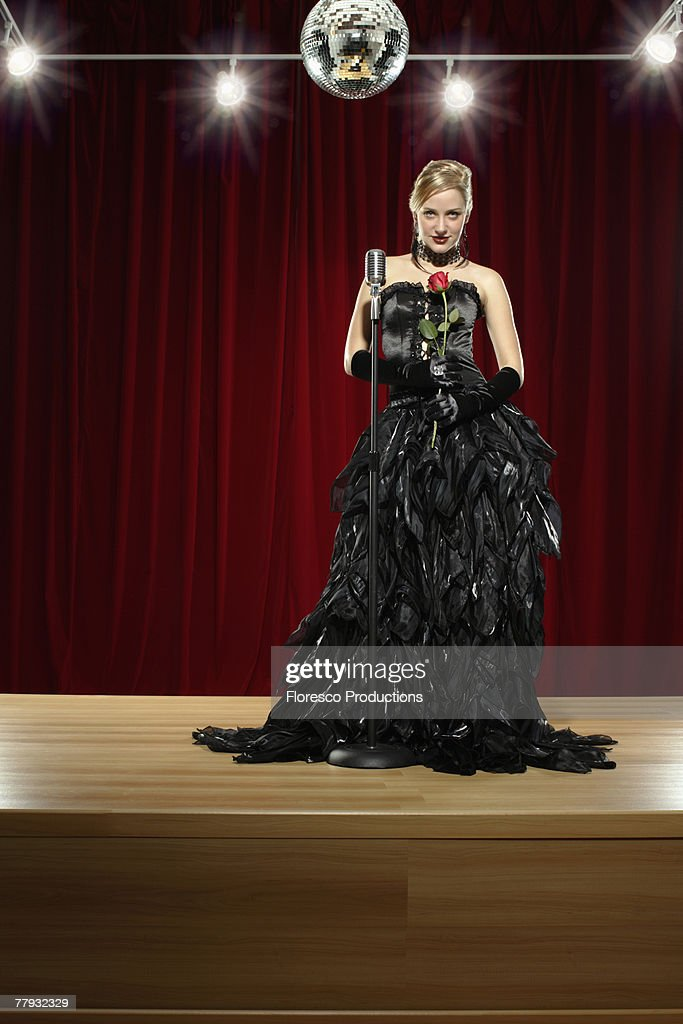 Woman with microphone on stage holding rose : Stock Photo