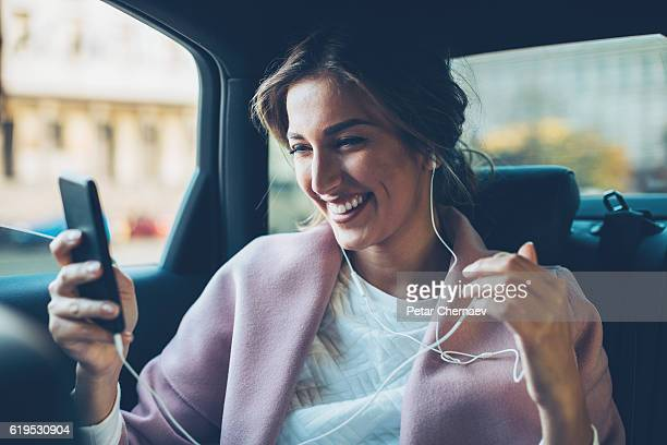 Woman with mobile phone in a car