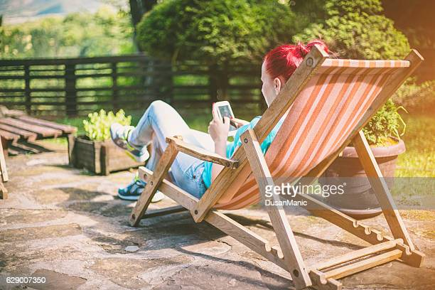 Woman with mobile phone resting on deck chair