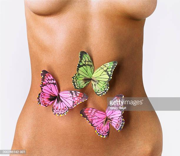 Woman with model butterflies over abdomen, mid section