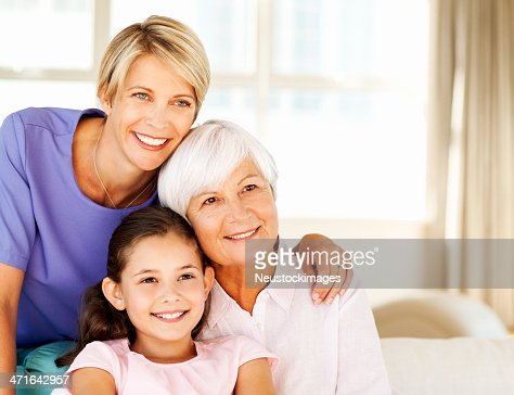 Woman With Mother And Daughter Looking Away In Living Room