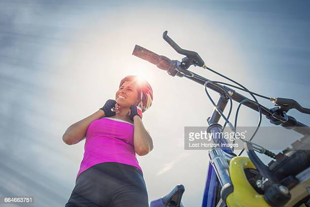 Woman with mountain bike putting her helmet on, Canton Wallis, Switzerland