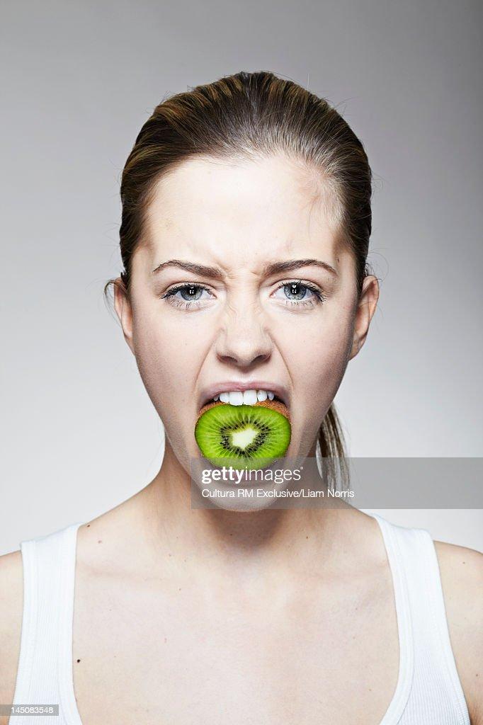 Woman with mouthful of kiwi