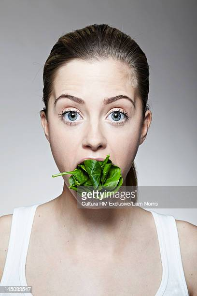 Woman with mouthful of lettuce