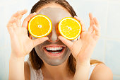 Beauty skin care cosmetics and health concept. Young woman with facial clay mask holding orange fruit slice covering eyes in bathroom