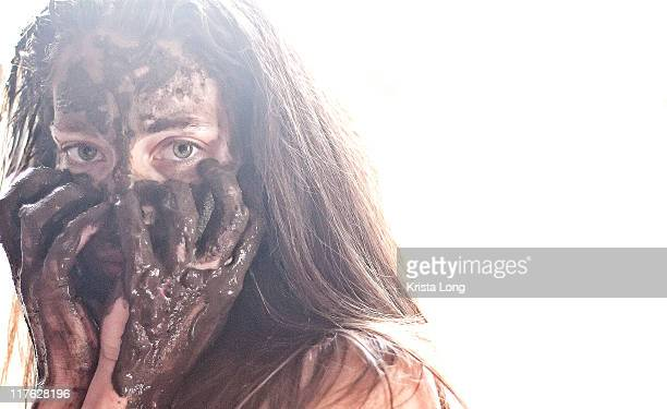 Woman with mud on her face and hands