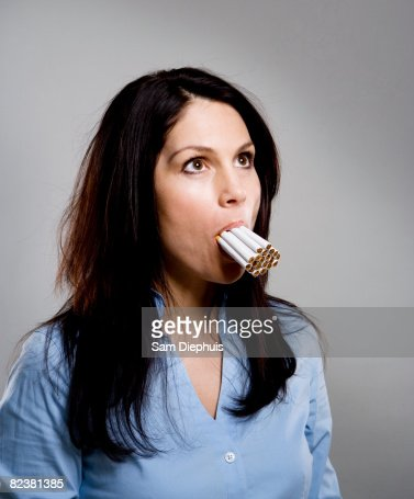 woman with multiple cigarettes in mouth stock photo