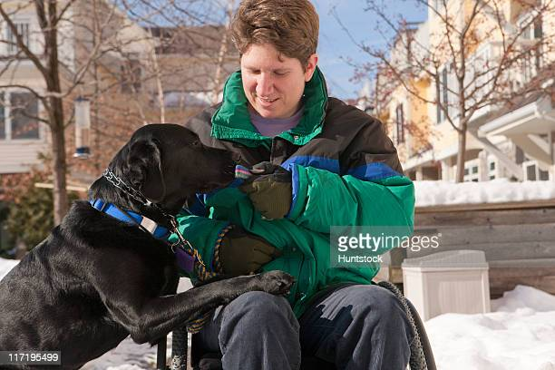 Woman with multiple sclerosis giving keys to a service dog in the snow