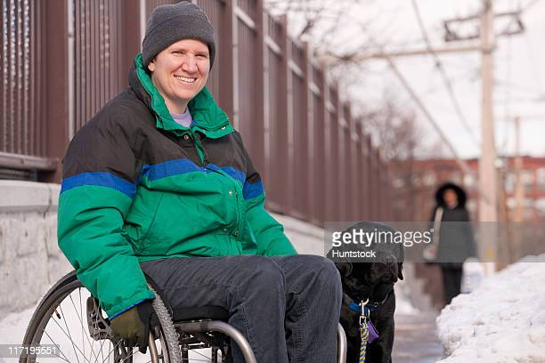 Woman with multiple sclerosis in a wheelchair with a service dog in winter snow
