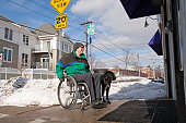 Woman with multiple sclerosis in front of a shop with a service dog