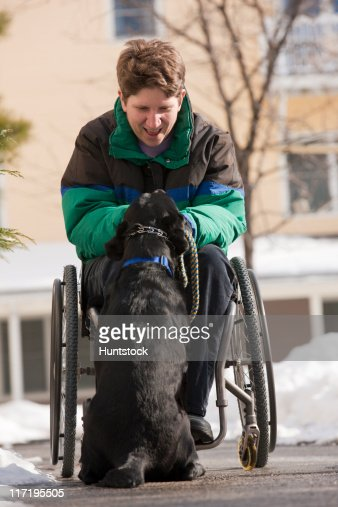 Woman with multiple sclerosis playing with a service dog in winter : Stock Photo