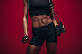 Woman with muscular abs holding jumping rope. Female fitness model with skipping rope on red background. Cropped shot in studio, focus on female's perfect torso.