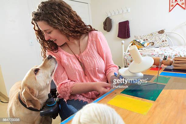 Woman with Muscular Dystrophy working with her knitting and talking to her service dog