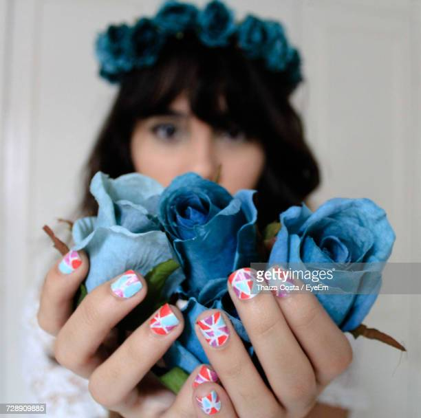 Woman With Nail Art Holding Artificial Blue Roses Against Wall