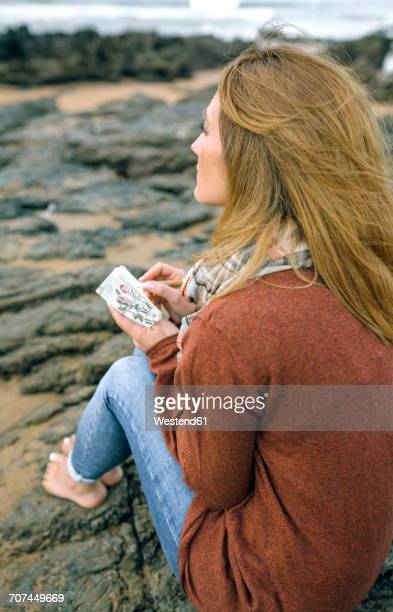 Woman with notebook sitting on rocks on the beach in winter