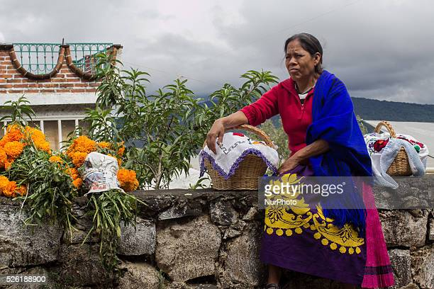 A woman with offerings and flowers takes a rest on her way to the cemetery of Janitzio on October 31 2015