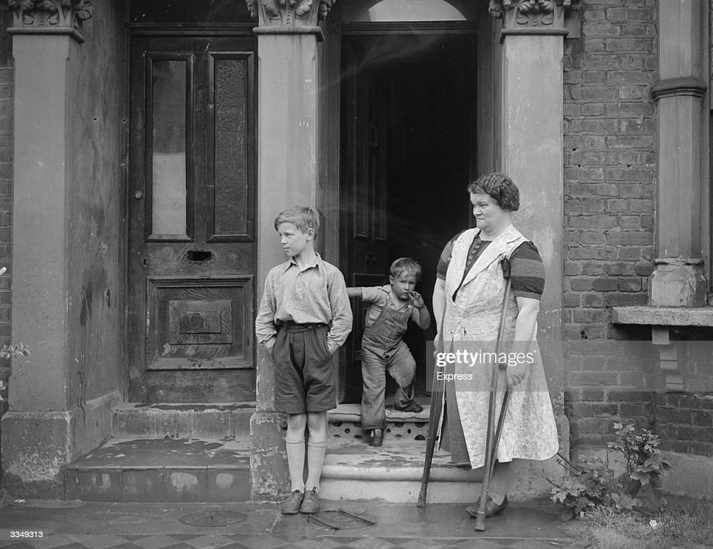 A woman with one leg standing on crutches with her two sons, in the doorway of their house.