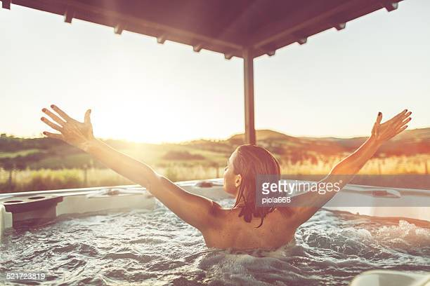 Woman with open arms in whirlpool jacuzzi