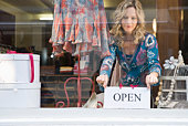 Woman with open sign at store window