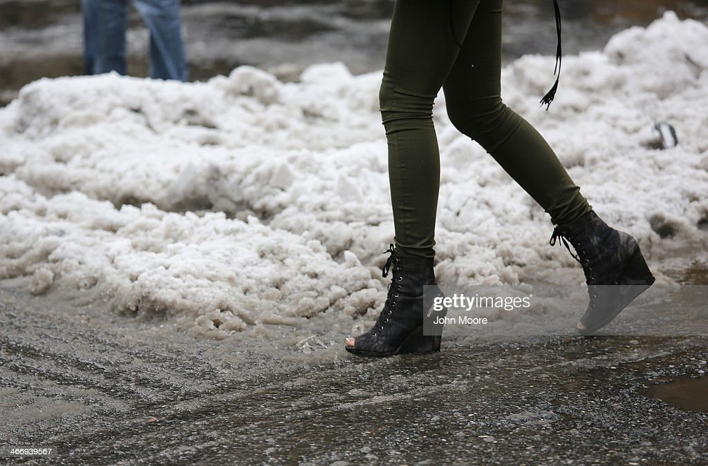 A woman with open toe boots navigates a slushy intersection near Union Square on February 5, 2014 in New York City, United States. New Yorkers, like millions of Americans in the northeast, dealt with the latest winter storm, which dumped 4 inches of snow on Central Park before turning to rain.