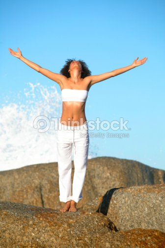 woman with outstretched arms and back to a breaking wave stock photo