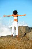 Woman with outstretched arms facing a breaking wave