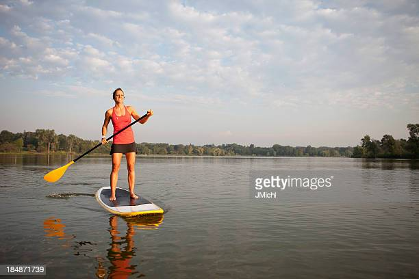 Woman with paddle stands on paddleboard in water