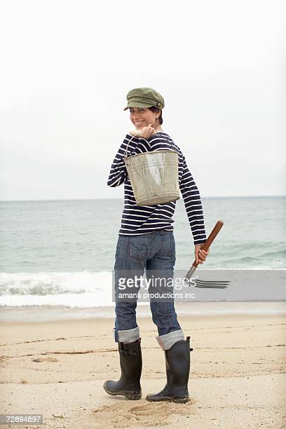 Woman with pail and pitchfork standing on beach