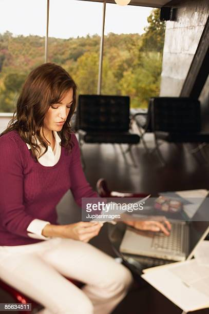 Woman with paperwork and laptop computer