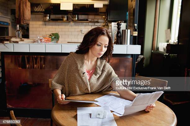 Woman with paperwork in restaurant