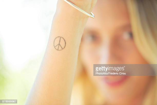 Woman with peace sign tattoo on her wrist