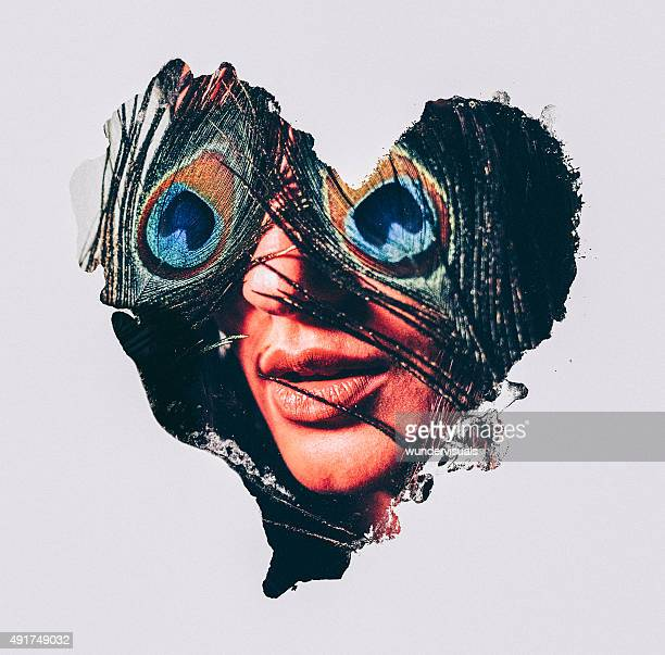 Woman with peacock feathers over her eyes in heart shape