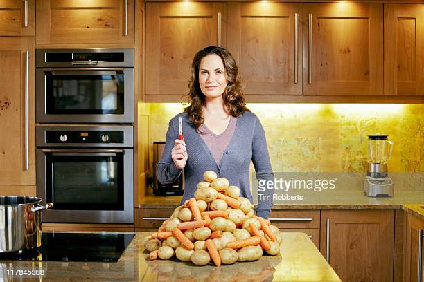Woman with peeler and large pile of vegetables.
