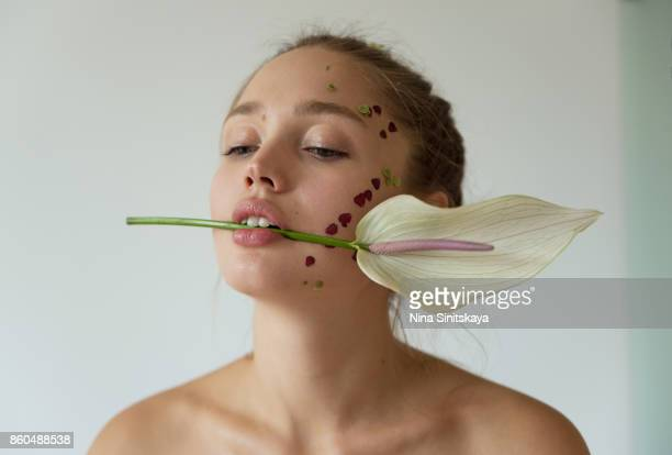 Woman with petals on face holding white flower between her teeth