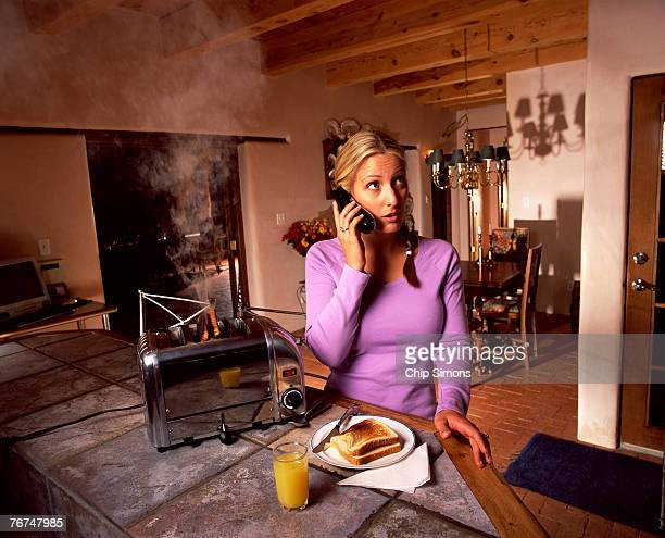 Woman with phone burning toast