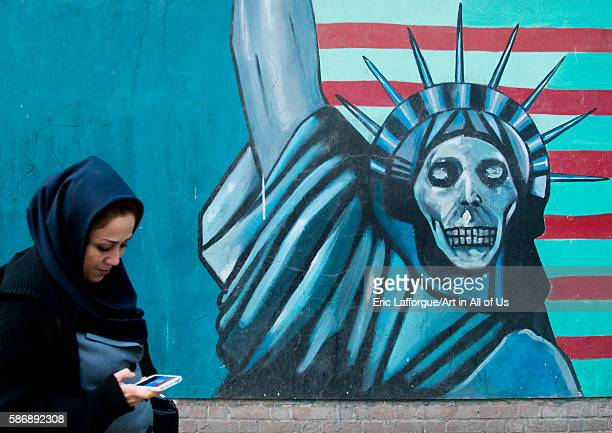 Woman with phone passing in front of an antiamerican propoganda slogan depicting statue liberty skeleton on the wall of the united states embassy...