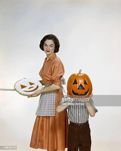 Woman with pie looking at child holding halloween pumpkin, smiling