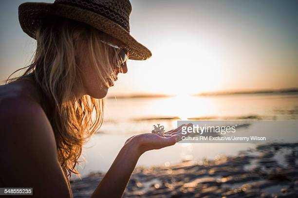 Woman with piece of coral in her hand, Gili Air, Indonesia
