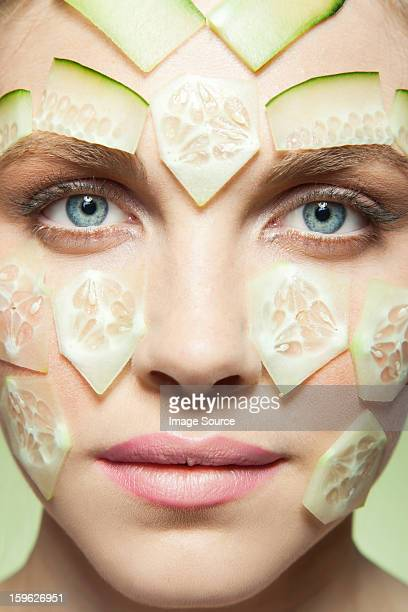 Woman with pieces of cucumber covering face