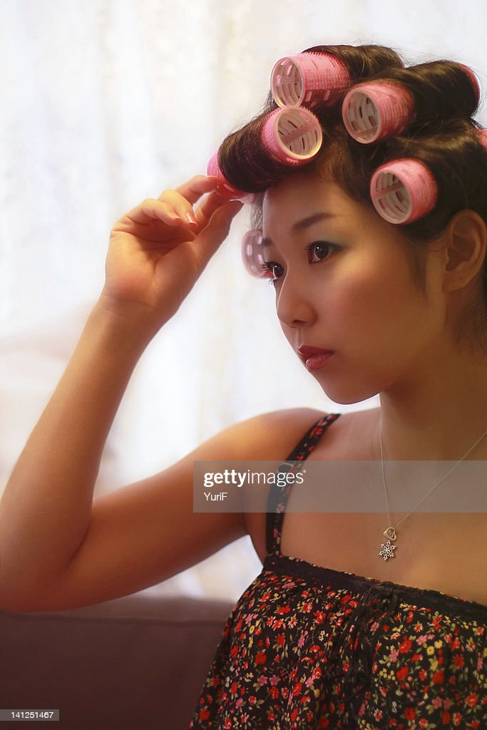 Woman with pink curlers : Stock Photo