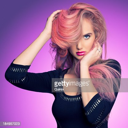 Woman with pink hair over one eye in a black dress
