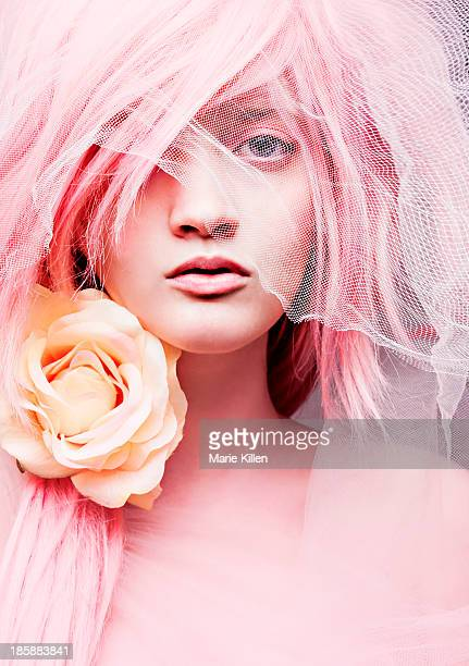Woman with pink hair, veil, and rose