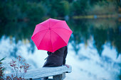 Woman with pink umbrella by lake, Bellingham, Washington, USA