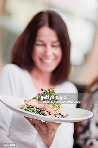 Woman with plate of food in cafe