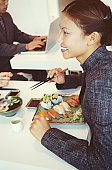 Woman with plate of sushi in restaurant, smiling