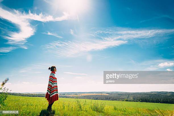 woman with poncho in summer landscape at early morning